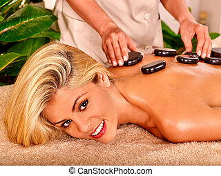 Woman getting massage - Stone massage of blond woman in spa...