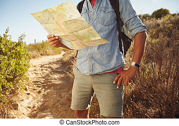 Man hiking in countryside with a map - Cropped shot of young...
