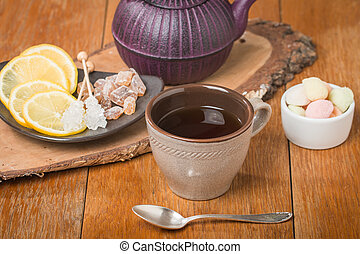 Tea with marmalade, chrystal sugar and lemon on wooden table