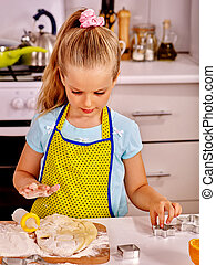 Child knead dough at kitchen - Child girl knead dough at...