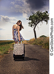 suitcase - girl with a suitcase on the old road between...