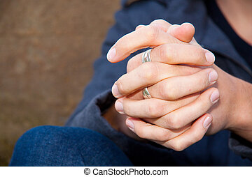 Hands Clasped - A mans hands are locked together with rings...