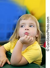 Blond little girl funny expression in her mouth