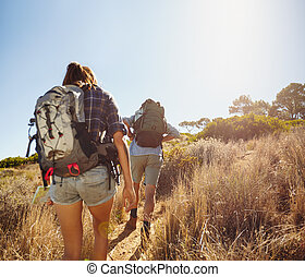 Hikers walking through mountain trial - Rear view image of...