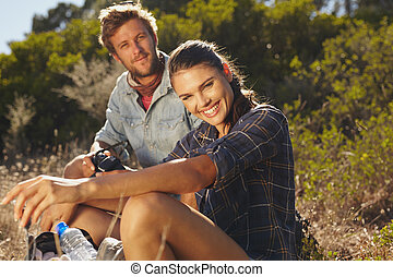 Happy couple taking a break on hike - Portrait of happy...