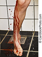 Leg and foot of boy in shower with blood running down