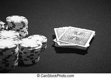 Poker cards and betting chips in a table game. Black and...