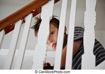 Boy looking scared through the handrail of a staircase