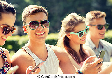 smiling friends with smartphones sitting in park -...