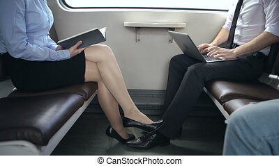 Train Trip Pastime - Mid-section of man and woman seated in...