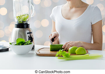 close up of woman with blender chopping vegetables - healthy...