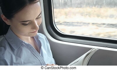Train Trip - Business woman in train checking her planner...