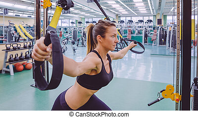 Woman doing suspension training with fitness straps -...