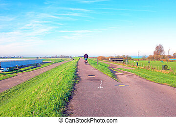Biking on the dyke near Amsterdam in the Netherlands