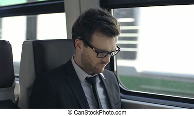 Window View - Close up of businessman sitting in train and...
