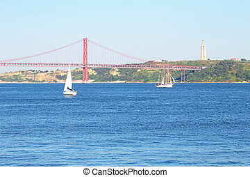 Sailing on the river Tejo with the 25 Abril bridge and the...