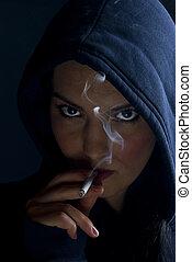 Woman hood smoking in dark