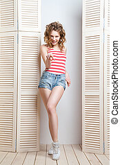 Young beautiful woman posing in front of a jalousie - Young...