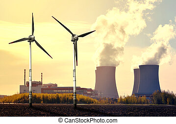 Nuclear power plant and wind turbines at sunset