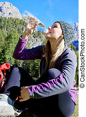 Woman after walk in the mountain in summer drinking water refreshing