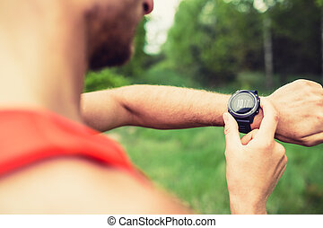 Runner looking checking sport watch - Runner on mountain...