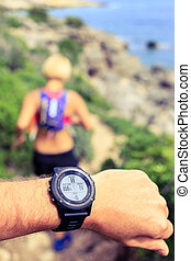 Runner looking at sport watch - Runner or hiker on mountain...