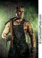 labour - Masculine dirty coal miner with a pickaxe over dark...