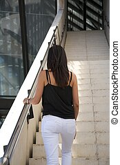 back woman upstairs - woman walking upstairs outside the...