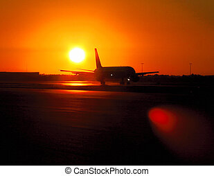 Airport sunrise - Plane landing at sunrise