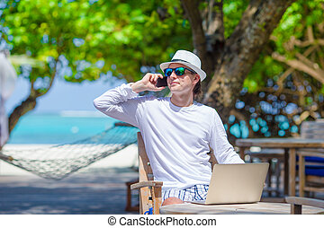 Young man calling by cell phone in outdoor cafe - Business...