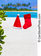 Red Santa hat and Christmas stocking hanging on tropical...