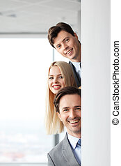 Happy business people looking out from corner in office