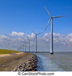 Row of wind turbines along a breakwater