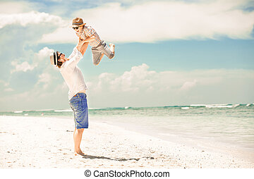 Happy father and son enjoying beach time on summer vacation...