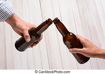 Beer Bottle Toast - A man and a woman toasting with beer...