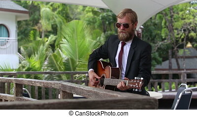 bearded man plays guitar by wooden barrier - light haired...