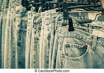 Row of Jeans and trousers on hangers.
