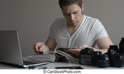 Photographer watching photo album - Male photographer...