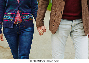 Romance - Young couple in casualwear holding by hands