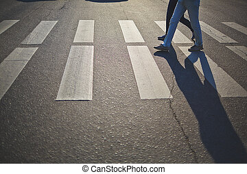 Crossing road - Urban couple in jeans and sports shoes...