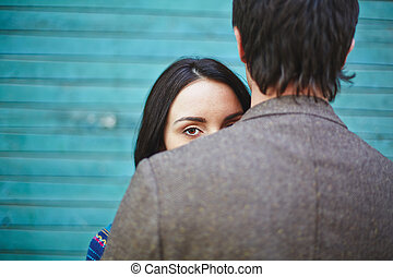 Glance - Young woman looking at camera out of man back
