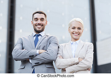 smiling businessman and businesswoman outdoors - business,...
