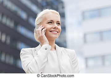 smiling businesswoman with smartphone outdoors - business,...