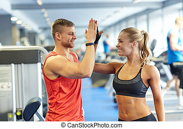 smiling man and woman doing high five in gym - sport,...