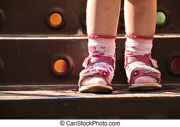 Baby legs in shoes and socks, standing on step of stairs...