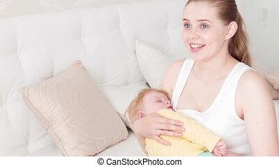 Happy mother hands her sleeping child
