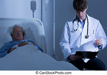 Looking at medical history - Young physician looking at his...