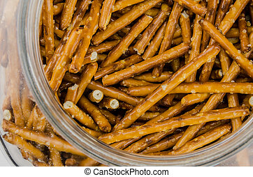 Pretzel Sticks in a Jar - A glass jar holds salted pretzel...