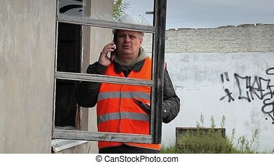 Construction inspector with cell phone near broken window