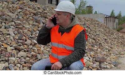 Construction inspector with phone at the pile of crushed...